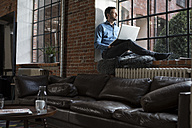 Mature man sitting on window sill, using laptop - RBF05541