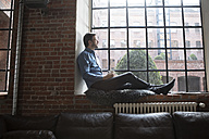 Mature man sitting on window sill, relaxing with cup of coffee - RBF05544