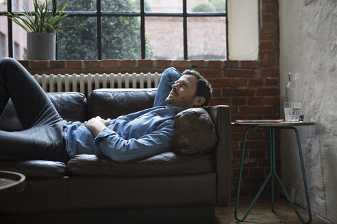 Man lying on couch, daydreaming - RBF05550