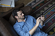 Man lying on couch, using smart phone - RBF05553