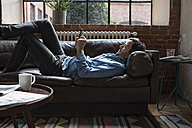 Man lying on couch, using smart phone - RBF05556