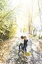 Two little boys playing on autumnal country road - VABF01025