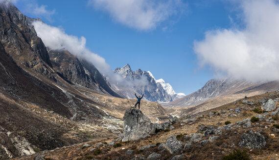 Nepal, Himalaya, Khumbu, Everest region, Khunde, woman cheering on rock - ALRF00839
