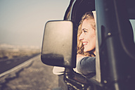Happy young woman looking out of car window - SIPF01332