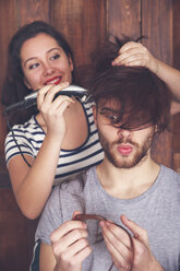 Young man getting a haircut by his girlfriend with hair cutting machine - RTBF00585