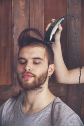Portrait of young man getting a haircut by his girlfriend with hair cutting machine - RTBF00588