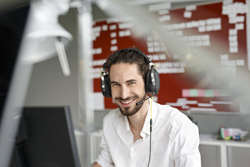 Smiling man in office with headset - PESF00394
