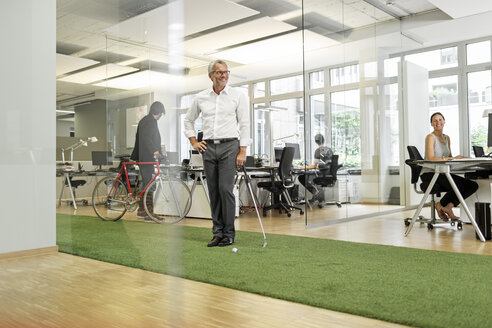 Businessman playing golf in office - PESF00409