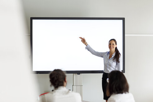 Smiling businesswoman leading a presentation - PESF00424