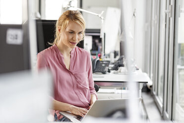 Woman using laptop in office - PESF00439