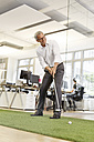 Businessman playing golf in office - PESF00457