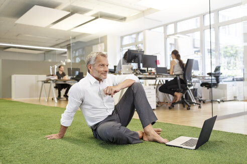 Businessman sitting on carpet in office with laptop - PESF00460