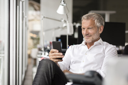 Smiling businessman looking on cell phone in office - PESF00508