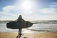 Back view of young woman with surfboard on the beach - KIJF01080