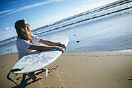 Young woman with surfboard crouching on the beach watching sunset - KIJF01083