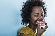 Portrait of young woman eating doughnut - UUF09779