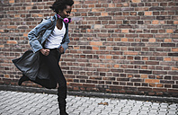 Smiling young woman with headphones and backpack running on pavement - UUF09791