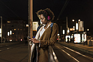 Young woman with headphones and smartphone waiting at the tram stop - UUF09806