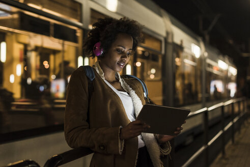 Young woman with headphones and tablet waiting at the tram stop - UUF09812