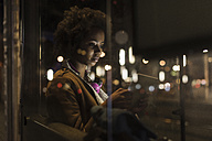 Young woman with tablet waiting at the tram stop by night - UUF09815