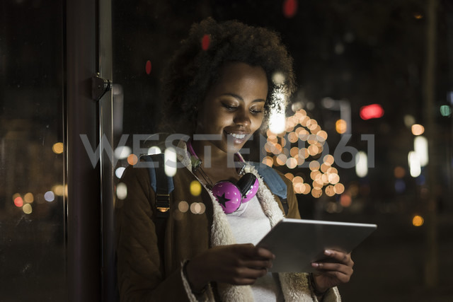 Young woman with headphones usinf tablet while waiting at the tram stop - UUF09818