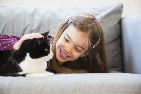 Portrait of happy little girl lying on couch stroking cat - LVF05787