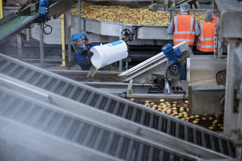 Worker wearing protective mask at apple distribution factory - ZEF12422
