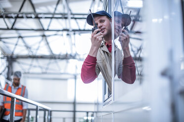 Worker with walkie-talkie instructing in factory - ZEF12434