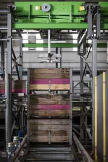 Group of crates stacked on machine in factory - ZEF12449