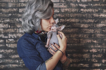 Young woman kissing Sphynx cat - RTBF00593