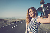 Spain, Tenerife, portrait of smiling young woman with longboard standing at empty country road - SIPF01338