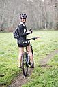 Portrait of happy woman with mountain bike - RAEF01657