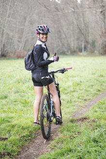 Portrait of happy woman with mountain bike - RAEF01657