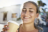 Portrait of smiling young woman with coffee to go - SRYF00198