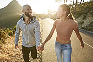 South Africa, Cape Town, happy young couple walking hand in hand at sunset - SRYF00234