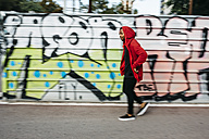 Young man wearing red hoodie passing a graffiti wall - JRF01161