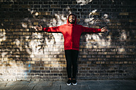 Young man wearing red hoodie standing at a wall with outstretched arms - JRFF01167