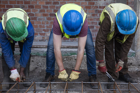 Construction workers on a construction site assembling reinforcing steel - ZEF12462
