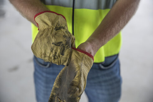 Construction worker putting on protective gloves - ZEF12471