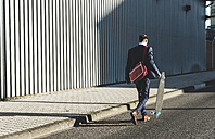 Young businessman walking with skateboard on the street - UUF09823