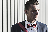 Portrait of young man outdoors wearing bow tie - UUF09826
