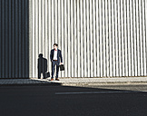 Young businessman standing on pavement looking around - UUF09829