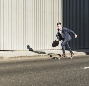 Young businessman riding skateboard on the street - UUF09841
