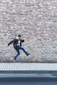 Young man jumping in front of brick wall - UUF09844