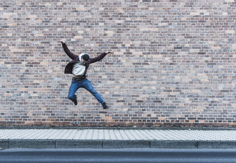 Young man jumping in front of brick wall - UUF09847