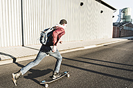 Young man riding skateboard on the street - UUF09856