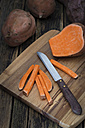 Sliced and whole sweet potato on wooden board - YFF00615