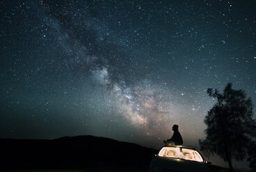 Austria, Mondsee, silhouette of man sitting on car roof under starry sky - WVF00790
