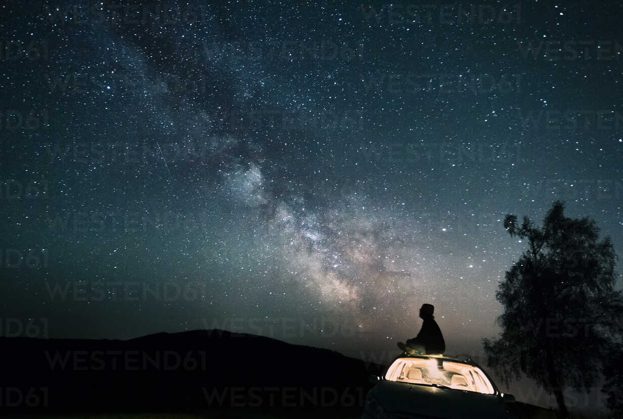 Austria, Mondsee, silhouette of man sitting on car roof under starry sky - WVF00790 - Valentin Weinhäupl/Westend61