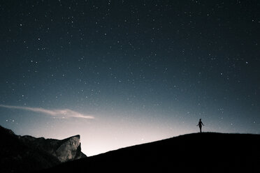 Austria, Mondsee, silhouette of woman standing under starry sky - WVF00805